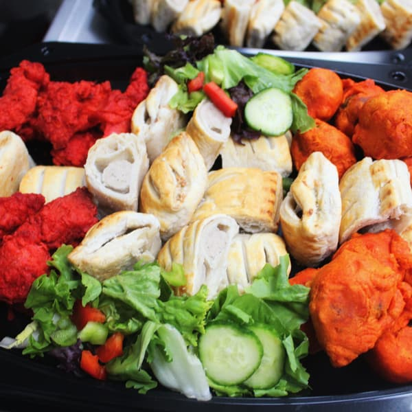 A selection of hot food from the buffet on a platter including pakora, sausage rolls and salad