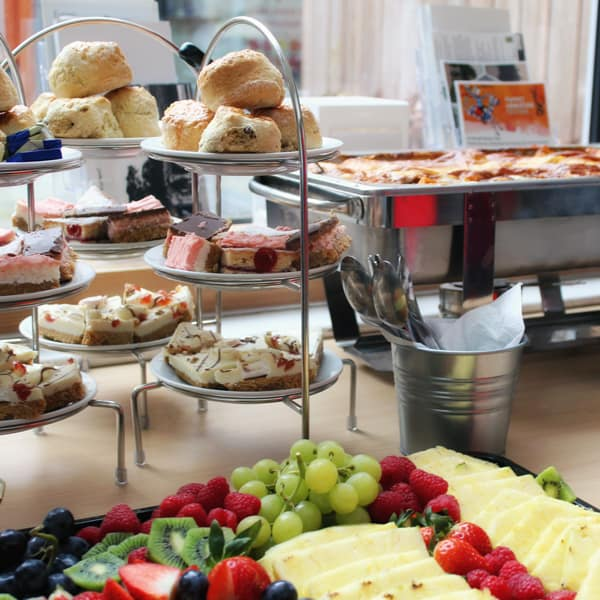 A selection of food from the Spoon buffet inculcating a cheese board with grapes and cake stands with treats such as scones and various cakes