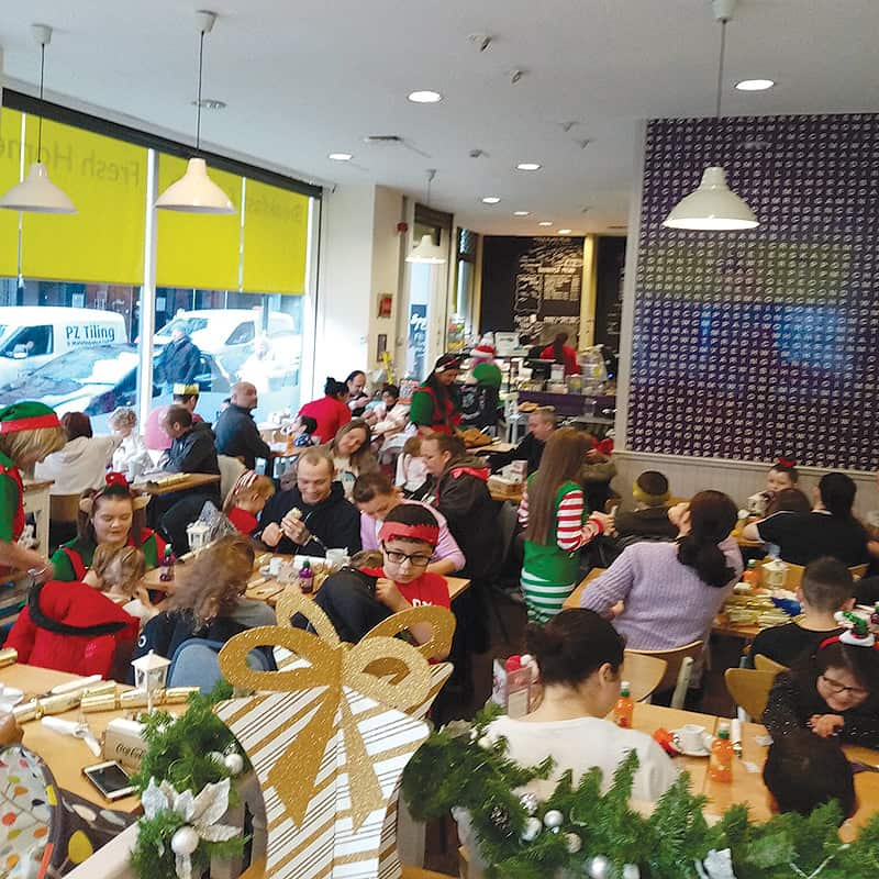 Lots of children in a busy Spoon cafe cafe enjoying a Christmas themed afternoon