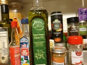 Inside of cupboard showing spices, olive oil, herbs and other products the article describes as essential basics